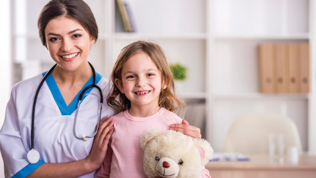 Nurse with young girl and teddy bear