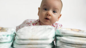 Baby staring at camera over a pile of diapers